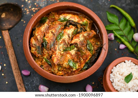 Top view Sardine fish curry spicy Woman hand take Kerala fish curry rice India, Indian food red chili, curry leaf. Asian cuisine. Delicious spicy, Bengali Goan fish curry coconut milk, mango clay pot.