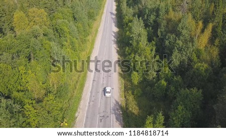 Top view scenic winding country road through green farmland. Clip. Aerial rural road countryside, blue sky #1184818714