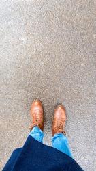 Top view selfie of woman feet in brown autumn boots on wet asphalt after rain.
