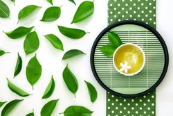 Top view shot of a hot cup of tea with green leaf decoration  on white background , Organic green Tea ceremony time concept