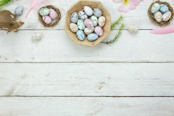 Top view shot of arrangement decoration Happy Easter holiday background concept.Flat lay colorful Easter egg with flower and rabbit doll on modern rustic white wooden at office desk.space for mock up