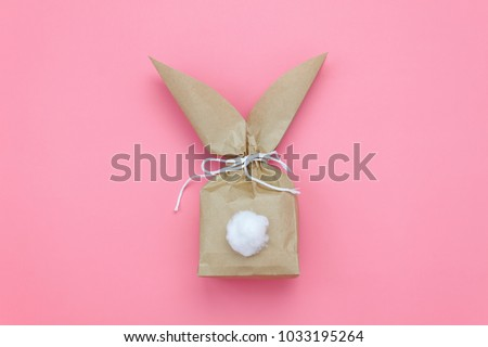 Top view shot of arrangement decoration Happy Easter holiday background concept.Flat lay minimalism paper bag same bunny or rabbit  for gift or present on modern pink paper at office desk.pastel tone.