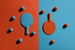 Top view shot of composition with ping pong rackets and balls placed on two toned surface