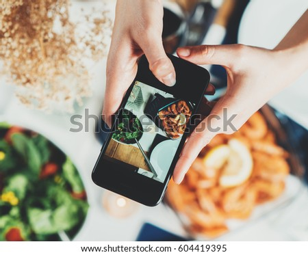 Top view shot of female hands taking a picture of food, young hipster girl making a photo of tasty mediterranean food table