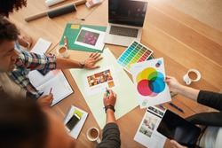 Top view shot of group of creative designers discuss the color palette during meeting. Creative team brainstorming around table.