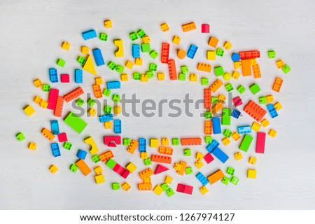 Top view shot of multicolored toys blocks, wooden bricks, lego, building game pieces of kids organize toys in various shape on isolated white wooden floor background