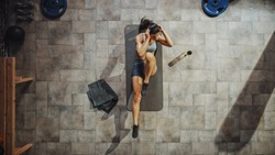 Top View Shot of Professional Female Bodybuilder Doing Bicycle Crunches while Lying on the Yoga Mat in the Hardcore Gym. Muscular and Athletic Beautiful Woman Muscle, Power and Cardio Workout.