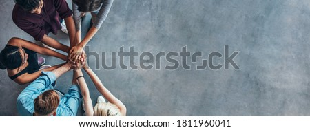 Top view shot of stack of hands. Young college students putting their hands on top of each other symbolizing unity and teamwork.