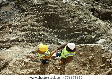 Top view shot of two industrial  workers wearing reflective jackets  shaking hands standing on mining worksite outdoors using digital tablet, copy space