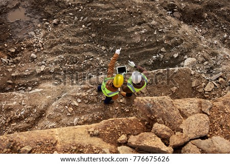 Top view shot of two industrial workers wearing reflective jackets standing on mining worksite outdoors using digital tablet, copy space