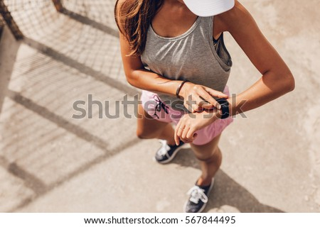 Top view shot of young woman checking fitness progress on her smart watch. Female runner using fitness app to monitor workout performance. #567844495