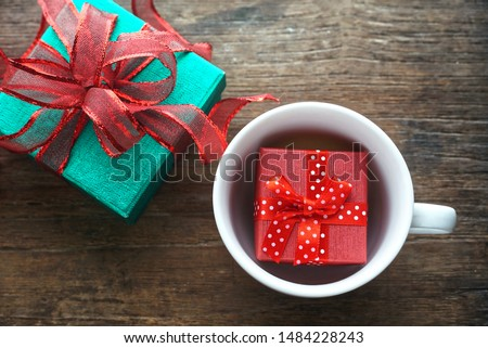 Top view small red gift box in coffee cup and green glitter gift box with red ribbon on wood table, christmas and happy new year theme.