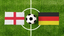 Top view soccer ball with England vs. Germany flags match on green football field.