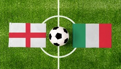 Top view soccer ball with England vs. Italy flags match on green football field.
