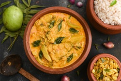 Top view spicy hot Bengali Rohu or King fish curry. Indian food. Fish curry with red chili, curry leaf. Asian cuisine. Woman hand take spicy Kerala, Goan fish curry coconut milk and mangoes clay pot