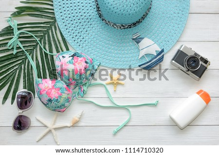 Top view. Summer Fashion woman swimsuit Bikini, camera, starfish, sunblock, sun glasses, hat. Travel and vacations in the holiday, wood white background. Summer Concept.