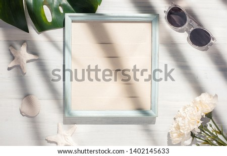 Top view summer picture frame with monstera leaf and seashell on white wood table with hard shadow light.summer vacation