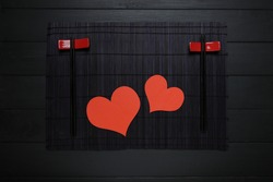 Top view, sushi sticks and two red hearts, as symbol of love on dark wooden table.