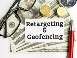 Top view text Retargeting and geofencing written on white paper note with compas,coins,fake money,pen and eye glasses.Business concept.