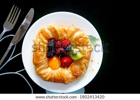 Top view the danish pastry fruits as black background. Dark tone. Stockfoto ©