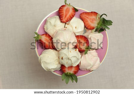 Top view the meringue cookies in a pink plate. Meringue cookies and strawberry slices. Crispy pink meringue. Meringue cookies made from egg whites and sugar. Mini pavlova or French baiser dessert.  Foto d'archivio ©