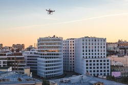 Top view to sunset cityscape of summer Moscow with orange sky, white building and shooting drone in the foreground