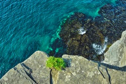 top view to the edge of a steep cliff with turquoise sea background on a summer day at sunrise . Nature and outdoor concept.