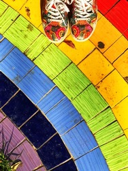 Top view to where I stand. Colourful sportswear shoes on tile floor designed as a rainbow.