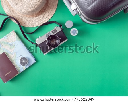 top view travel concept with retro camera films, map, passport, smartphone, compass and luggage on green background with copy space, Tourist essentials, vintage tone effect