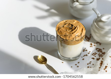 top view trendy dalgona coffee in glass with shadow on white background, iced coffee, whipped coffee, korean coffee concept