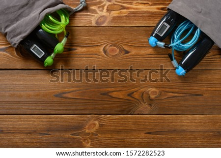 top view two sets skipping ropes with digital counters on wood background