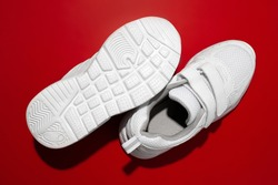 top view two white kid sneakers with velcro straps with hard sun shadows on a red background, one sneaker lies with the sole up.