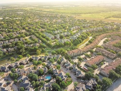 Top view urban sprawl in Dallas-Fort Worth area. Apartment building complex and suburban tightly packed homes neighborhood with driveways flyover. Vast suburbia subdivision in Irving, Texas, US