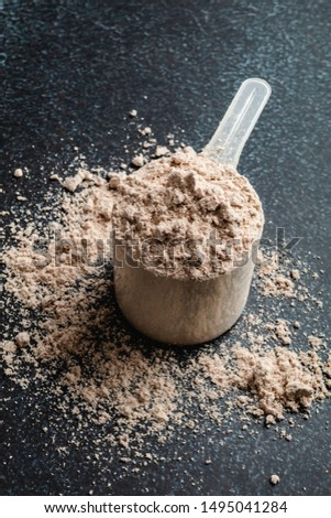 Top view whey protein scoop on dark background, copy space