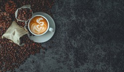 Top view, White coffee cup of hot latte art coffee and coffee bean placed on dark stone background. Menu in coffeeshop, relaxing time holidays.
