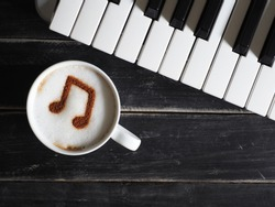 Top view white cup of coffee with musical note symbol on frothy surface flat lay on black painted wood table with keyboard. Enjoy coffee and music, Food art creative concept / close up, space for text