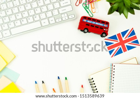Top view white desk with blank spiral notepads, keyboard, British bus toy and Britsh flag. Foreign learning concept