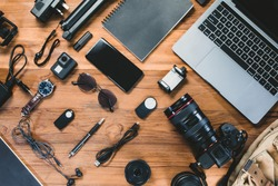 Top view with a digital camera, charger, camera, lens, video camera, USB, personal laptop, book, pen, glasses, remote control, and electronics camera accessory photography concept on wooden background