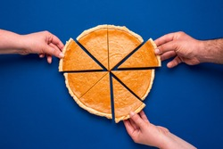 Top view with a home-baked pumpkin pie isolated on a blue colored background. Three people grabbing with their hand's slices of pumpkin cake
