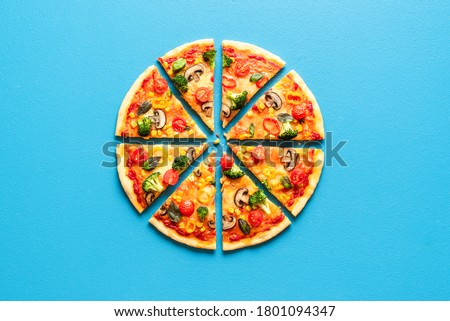 Top view with a sliced pizza primavera on a blue table. Vegetarian pizza flat lay. Sliced pizza isolated on a blue colored background.