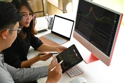 Top view with Asian businesswoman and colleague friend analyze trend chart stock market that show on tablet and computer, empty screen of laptop.