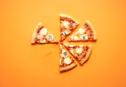 Top view with plain pizza slices on orange background. Flat lay with a sliced pizza. Vegetarian pizza made with four types of cheese and tomato sauce as toppings. Homemade pizza
