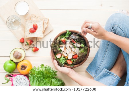 Top view woman eating chicken salad with fruits, vegetables, whole wheat bread and milk on wooden background, Healthy food