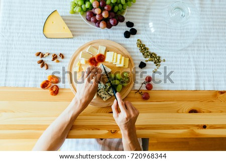 Top view woman's hands cutting cheese on wooden cutting board on wooden table with grapes and dried fruits, nuts, pumpkin seeds on wooden cheese plate on wooden table with strip tablecloth. Lay flat