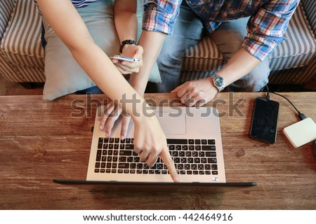 top view women touching screen phone and man typing laptop on wood table, internet of things.Couple people working  while discussion and shopping online together with credit card, relationship at home