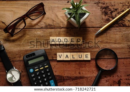 """Top view wood text """"Added value"""" with brown glasses,calculator,gold pen,black watch,magnifying glass and white pot plant.For Thinking Business Plan concept.Have copy space"""