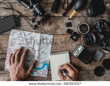 Top view work space of photographer  with hands is marking location on guide map, with digital camera, tripod, memory card, and camera accessory on wooden background.