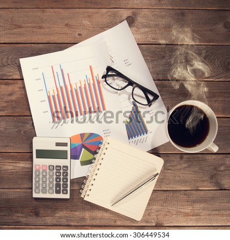 Top view workspace with booklet, pen, glasses, cup of coffee and graphs. Wooden table background in vintage toned.