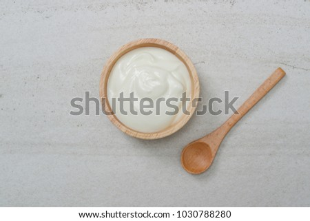 Top view yogurt in bowl on the white stone.