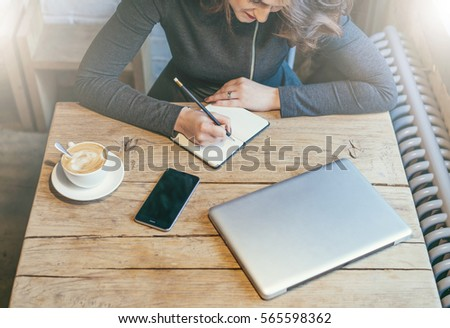 Top view. Young business woman sitting at wooden table in cafe and making notes in notebook. Nearby is cup of coffee, smartphone with blank screen and closed laptop. Student learning online. #565598362